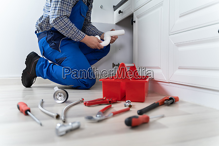 male plumber in overall fixing sink