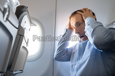man having anxiety attack in airplane