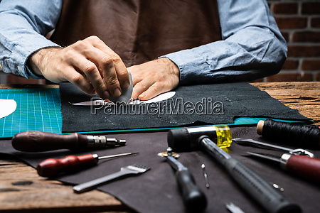 shoemaker working with leather at workshop