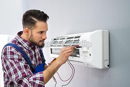 technician testing air conditioner