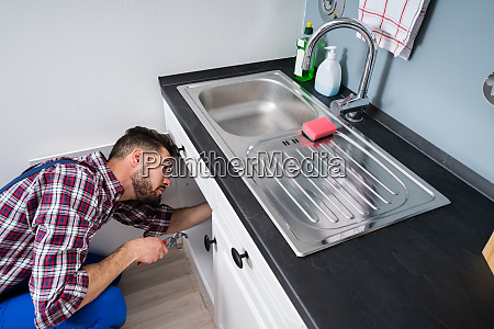 plumber in overall fixing sink pipe