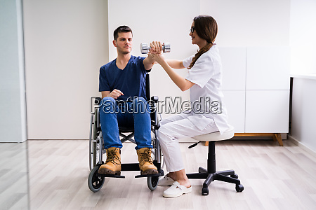 therapist assisting disabled patient while doing