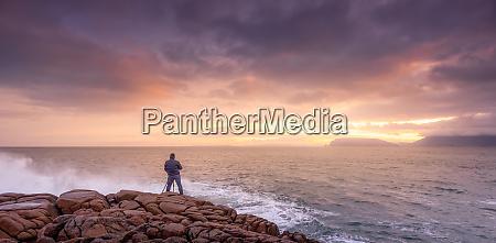 photographer photographing waves crashing on rocks