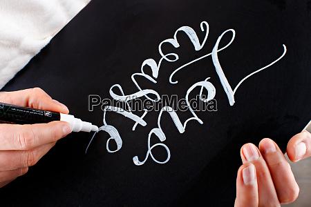 woman writing on a small chalkboard