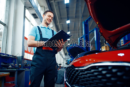 worker with a checklist car service
