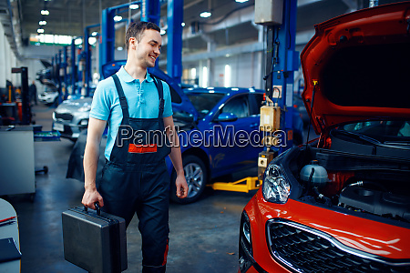 worker holds a toolbox car service