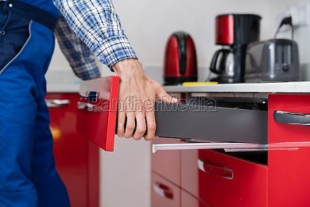 male carpenter installing drawer