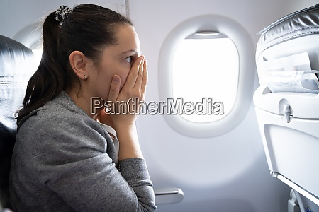 woman having anxiety attack in airplane