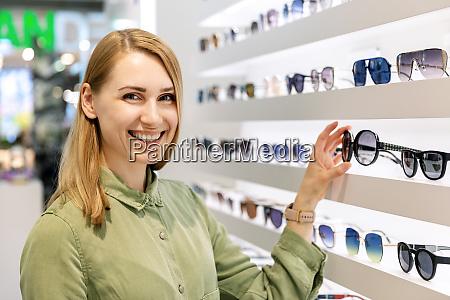 smiling woman choosing sunglasses from shelf