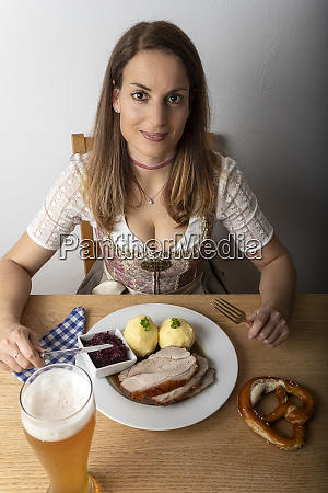 woman with a dirndl eating roasted