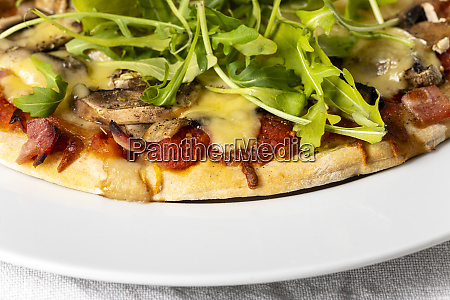 pizza on a plate with arugula