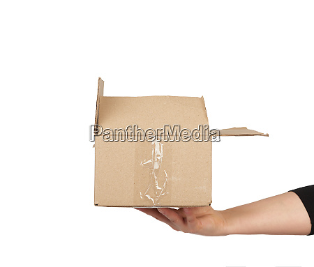 hand holds a brown cardboard box