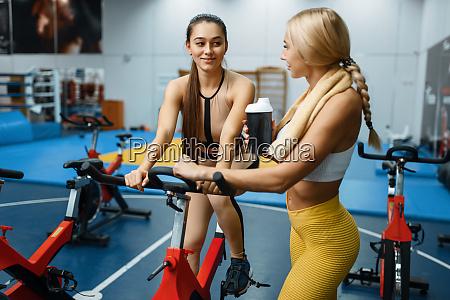 sportive girlfriends on stationary bikes in