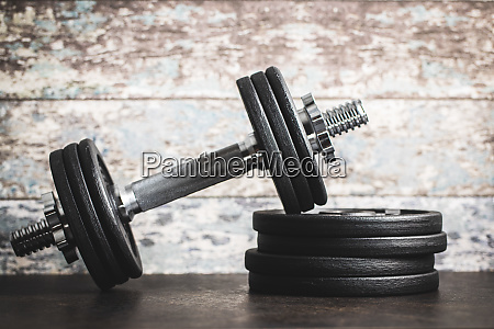 iron dumbbells before old wooden wall
