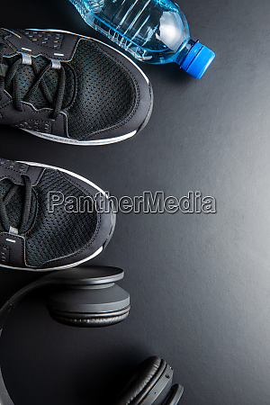 fitness concept black sports shoes headphones