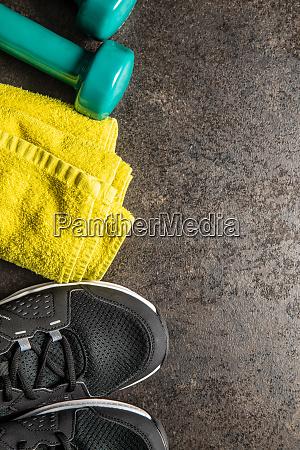 fitness concept black sports shoes dumbbells