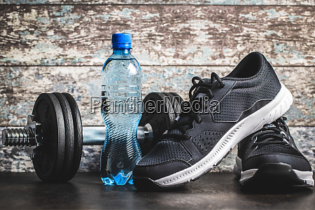 fitness concept black sports shoes dumbbell