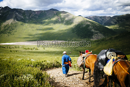guides and travelers ride horses into