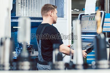 worker in industrial workshop programming a