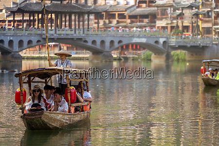 tourists in old wooden boats in