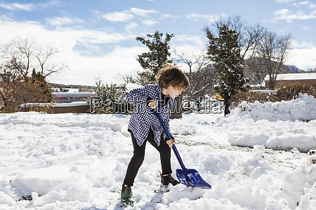 a young boy shoveling snow in