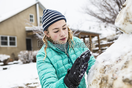 a teenage girl building a snowman