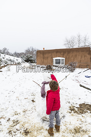 a young boy building a snowman