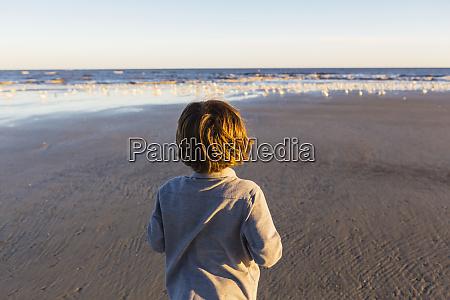 a boy walking on a beach