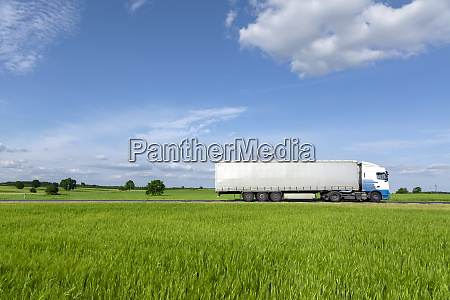 white transport truck driving on the