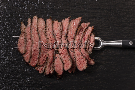 slices of a steak on slate
