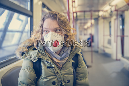 woman in subway with respirator on