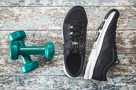black sport shoes and green dumbbells