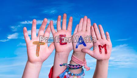 children hands building word team blue