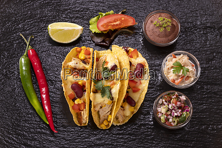 three mexican tacos on slate
