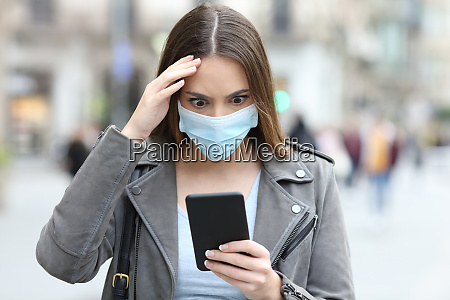 worried woman with mask checking phone