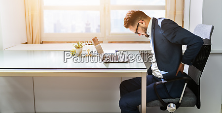 businessman sitting on chair suffering from