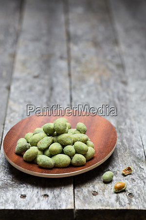 wasabi peanuts on rustic wooden background