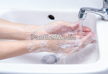 woman washing hand with soap foam