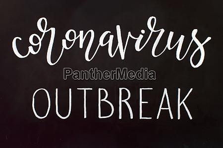 chalk inscription coronavirus outbreak on a