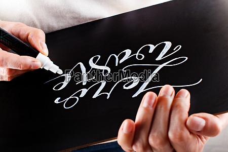 woman, writing, on, a, small, chalkboard - 28203949