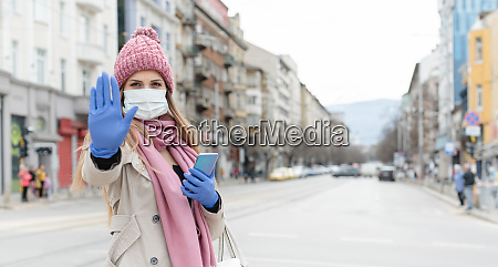 woman wearing corona mask giving stop