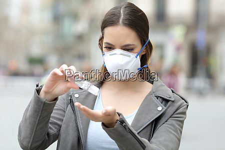 girl with mask applying hand sanitizer