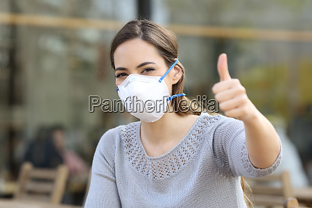 woman doing thumbs up wearing protective