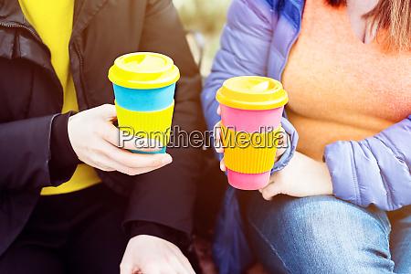 two women with reusable coffee mug