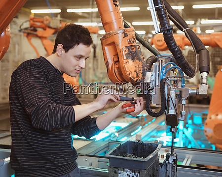 engineer performs maintenance of industrial robot
