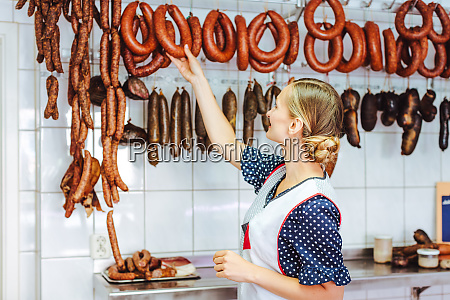 saleslady getting sausages from the hook
