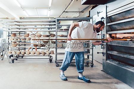 baker checking bread in the baker