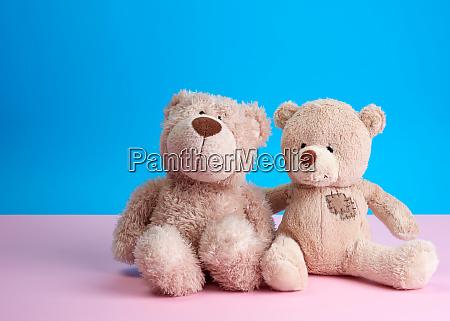 two teddy beige bears sitting huddled