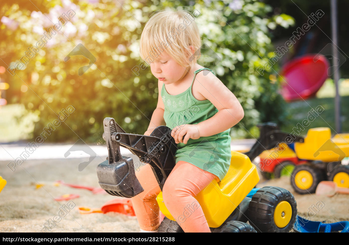 child, riding, on, a, toy, tractor - 28215288