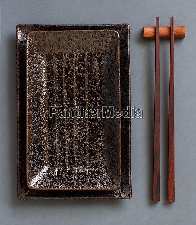 chopsticks and rectangular plates on dark